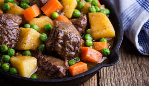 Beef and vegetable stew with potatoes in cast iron skillet on rural table