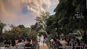 a crowd of people at a park: A couple got married while the Taal Volcano erupted in the background.