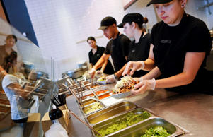 Employees prepare orders for customers at a Chipotle Mexican Grill Inc. restaurant in Hollywood, California on Tuesday, July 16, 2013.