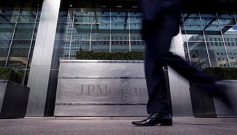 A pedestrian walks past the offices of JPMorgan Chase & Co. in the business and financial district of Canary Wharf in London, U.K., on April 10, 2012.