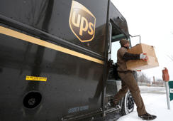A UPS driver steps off his truck to deliver packages in Evanston, Illinois, March 5, 2014.