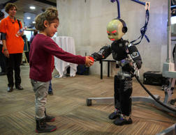 A girl gives a ball to a humanoid robot during the International Conference on Humanoid Robots in Madrid November 19, 2014.