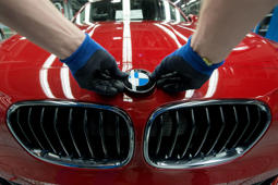 A worker fixes the logo of German car maker BMW on a BMW car at the company's plant in Regensburg, southern Germany, on March 13, 2014.