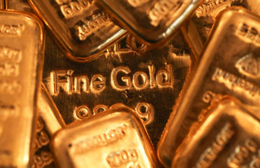 One hundred gram gold bars sit on a one kilogram gold bar, center, in this arranged photograph at Gold Investments Ltd. bullion dealers in London, July 15, 2014.
