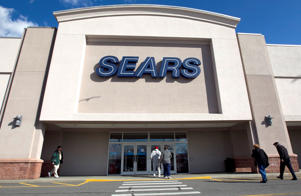 a person standing in front of a building: Sears