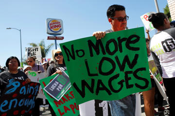 Fast food workers and supporters organized by the Service Employees International Union (SEIU) protest for a $15 per hour wage outside of a Burger King restaurant in Los Angeles, California, U.S., on Thursday, August 29, 2013. Fast-food workers in 50 U.S. cities plan to walk off the job today, ratcheting up pressure on the industry to raise wages and demanding the right to wages of $15 an hour, more than double the federal minimum of $7.25. Photographer: Patrick T. Fallon/Bloomberg