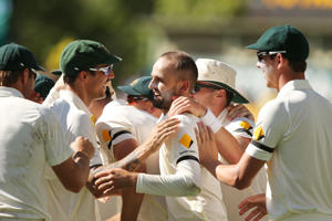 Nathan Lyon of Australia celebrates with teammates after he got the wicket of Virat Kohli of India during day five of the First Test match between Australia and India at Adelaide Oval on December 13, 2014 in Adelaide, Australia.