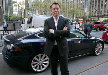 SpaceX billionaire founder and chief executive, and Tesla Motors CEO Elon Musk, poses beside a Tesla in New York City.