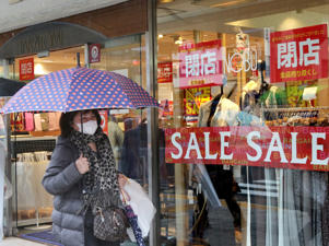 A pedestrian passes before an apparel shop which has a closing-down sale in Tokyo on November 26, 2014. Japan's economy shrank between July and September, the second consecutive quarterly contraction, in the wake of an April sales tax rise that was designed to help pay down one of the world's largest public debt mountains. AFP PHOTO / Yoshikazu TSUNO (Photo credit should read YOSHIKAZU TSUNO/AFP/Getty Images)