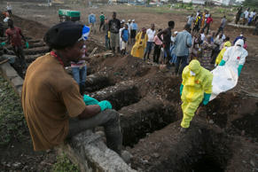 A grave digger watches as health workers carry the body of an Ebola victim for burial at a cemetery in Freetown, Sierra Leone, December 17, 2014. The death toll in the Ebola epidemic has risen to 6,915 out of 18,603 cases as of Dec. 14, the World Health Organization (WHO) said on Wednesday. There are signs that the increase in incidence in Sierra Leone has slowed, although 327 new cases were confirmed there in the past week, including 125 in the capital Freetown, the WHO said in its latest update.