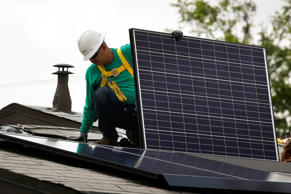 A SolarCity Corp. employee installs a solar panel on the roof of a home in the Eagle Rock neighborhood of Los Angeles, Calif. on  May 7, 2014.
