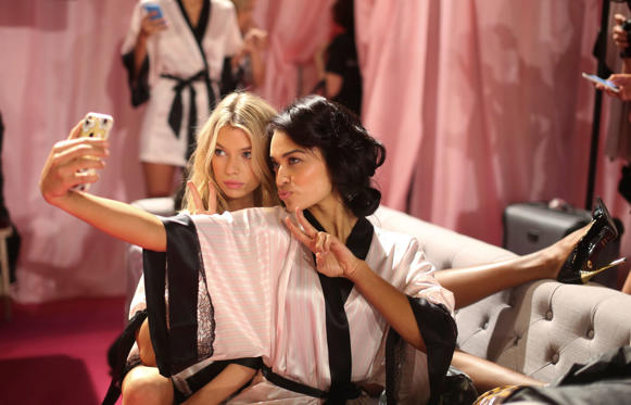 Slide 1 of 21: Shanina Shaik, right and Doutzen Kroes, both Victoria's Secret angels, wear dressing gowns produced by Victoria's Secret, as they pose for a selfie photograph during a hair and make-up session ahead of the 2014 Victoria's Secret Fashion Show in London, U.K., on Tuesday, Dec. 2, 2014. Earlier this month L Brands Inc., the owner of the Victoria's Secret lingerie brand, raised its third-quarter earnings forecast.