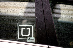 The Uber Technologies Inc. logo is displayed on the window of a vehicle after dr...