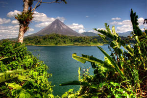 Arenal Volcano framed with wild banana leaves and the north shore of Lake Arenal in Costa Rica.