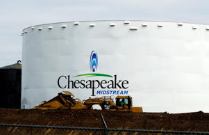 Earth-moving machinery builds up a berm around a Chesapeake Energy storage tank, near Dilley, Texas in this May 16, 2011 file pic.