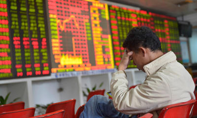 An investor sits in front of an electronic board showing stock information at a brokerage house in Haikou, Hainan province, China.