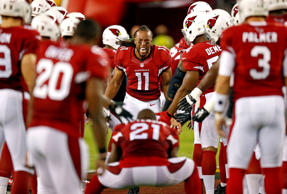 Arizona Cardinals wide receiver Larry Fitzgerald runs towards Patrick Peterson (21) as he takes the field before a game against the San Diego Chargers on Sept. 8, 2014, in Glendale, Ariz.