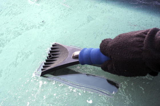 Slide 1 of 46: A driver wearing gloves scraping the ice off his windshield in the morning