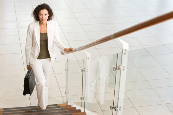 Lysbilde 1 av 14: A young businesswoman is smiling and walking up office stairs and holding a briefcase.