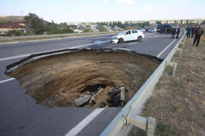 A car lies in a sinkhole in the road outside the Crimean capital Simferopol, September 28, 2014.