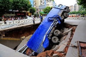 Workers stand next to a truck which is stuck in a large pit caused by a cave-in on a street in Wuzhou, Guangxi Zhuang Autonomous Region, August 14, 2014.