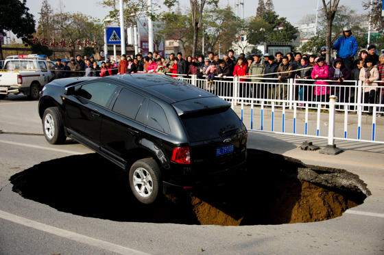 Lysbilde 1 av 23: A car halts on the verge of a five metres (16.4 feet) wide and two metres (6.5 feet) deep hole at Yunlianghe Road on December 12, 2014 in Zhenjiang, Jiangsu Province of China.