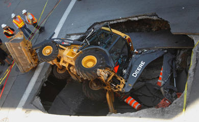 A construction vehicle lies where it was swallowed by a sinkhole on Saint-Catherine Street in downtown Montreal, August 5, 2013.