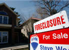 File photo of a foreclosure sign sitting atop a for sale sign in front of a single-family home in Denver, Colo in 2010
