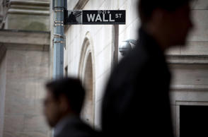 Pedestrians walk past a Wall Street sign and security camera in front of the New...