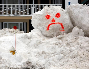 A snowman's face is seen in front of a hotel on Wednesday, Feb. 18, 2015, in Hampton, N.H., where several feet of snow has fallen in the last couple of weeks.  Jim Cole/AP Photo