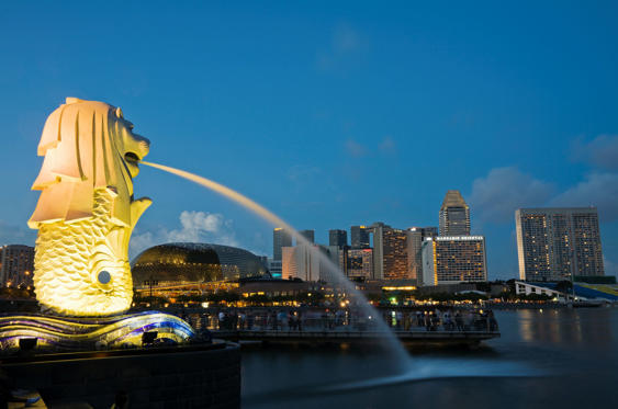 Symbol of Singapore at dusk the Merlion statue stands by the waterfront.