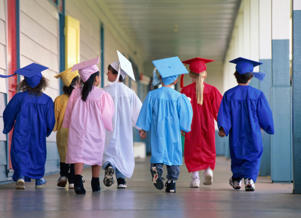 Group of young children wearing graduation robes