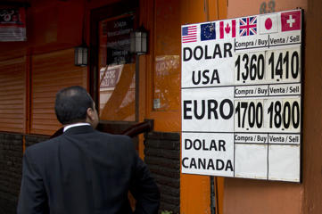 A man looks at the Mexican Peso exchange rates at a money exchange office in Mexico City, Friday, Dec. 12, 2014. Mexico is ready to intervene in currency markets to fight the peso's fall against the dollar amid concerns over dropping oil prices and a possible increase in U.S. interest rates.