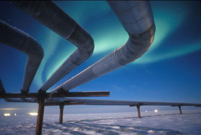 A full moon helps illuminate the Alaskan pipeline under the faint glow of the Aurora Borealis.