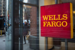 Pedestrians walk past a Wells Fargo & Co. bank branch in New York on Monday, Dec. 8, 2014.