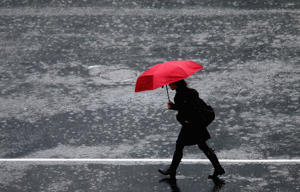 A pedestrian crosses in the intersection of Queen Street and Victoria Street during heavy rain in Auckland, New Zealand.