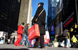 A woman holding her shopping bags makes her way in Times Square in New York on November 21, 2014. The National Retail Federation said last month it expects overall holiday sales this year to rise to $616.9 billion, a 4.1 percent increase from last year's level.