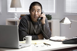 Chinese businessman talking on telephone at desk