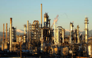 An oil refinery is seen at sunrise with the Rocky Mountains in the background in...