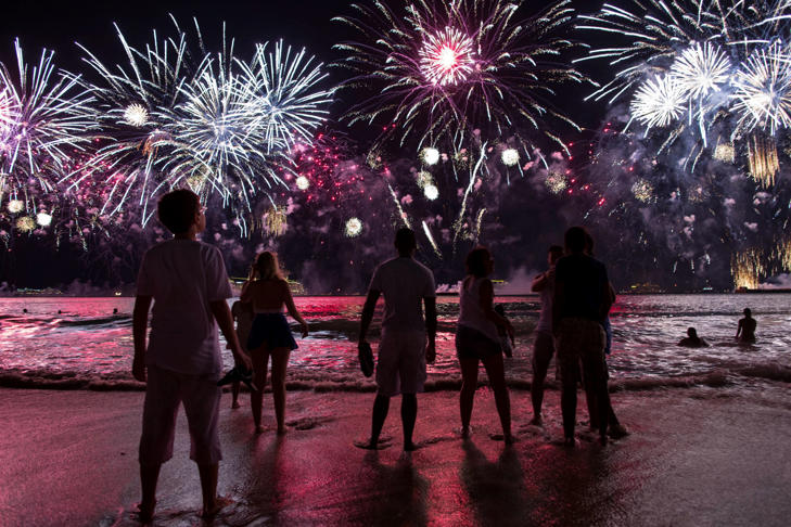 People watch fireworks exploding over Copacabana beach during New Year celebrations in Rio de Janeiro, Brazil,  Jan. 1, 2015.