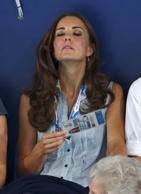 Catherine, Duchess of Cambridge fans herself with her Commonwealth Games accredi...