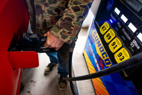 A customer pumps fuel at a Sunoco Inc. gas station in Rockbridge, Ohio, U.S., on Wednesday, Dec. 17, 2014. Retail gasoline prices have fallen about 24% this year, yet crude oil and wholesale gasoline price declines have been more profound, highlighting an inconsistent relationship.