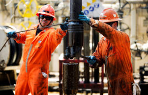 Workers change a drill pipe on the Laurus oil drilling rig operated by Petroleos...