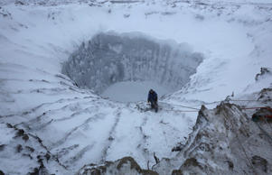 A member of an expedition group stands on the edge of a newly formed crater on the Yamal Peninsula, northern Siberia November 9, 2014.