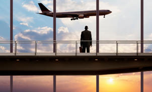 Businessman watching plane in sky.