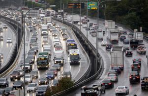 Traffic creeps along toward downtown on Interstate 5, left, and remains slowed down heading out during the rainy morning commute Wednesday, Sept. 24, 2014, in Seattle. The first fall rainstorm in Western Washington kept gutters running overnight, slickened roads, revived lawns and reminded residents the warm, dry summer is over. In the 24 hours ending at 6 a.m. Wednesday, the National Weather Service reported 0.98 inch of rain at Sea-Tac Airport, 1.13 inches at Olympia and 0.60 at Everett. (AP Photo/Elaine Thompson)