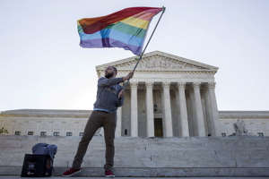 Vin Testa of Washington, DC, waves a gay rights flag in front of the Supreme Court. Joshua Roberts/Reuters