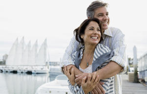 Smiling mature man embracing woman on pier