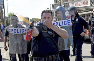 A law enforcement officer uses pepper spray to disperse the crowd at the intersection of North and Pennsylvania Avenues in Baltimore, May 4, 2015.