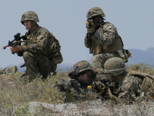 U.S. troops take their positions during a combined assault exercise at a beach facing one of the contested islands off the South China Sea known as Scarborough Shoal in the West Philippine Sea, April 21, 2015 at the Naval Education and Training Command at San Antonio township, Zambales province, northwest of Manila, Philippines.